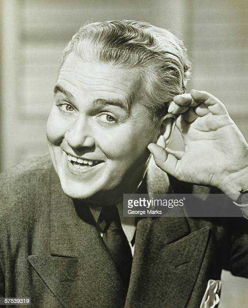 Man cupping hand to ear, posing, smiling, (B&W), portrait