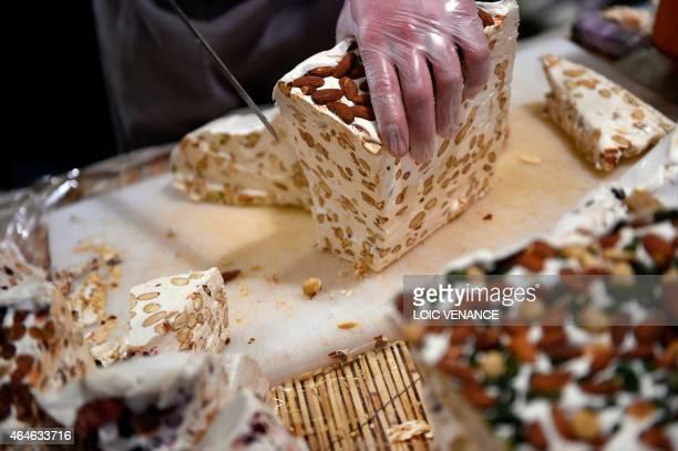 A man cuts nougat during the Paris international agricultural fair at the Porte de Versailles exhibition center in Paris on February 26 2015 AFP...