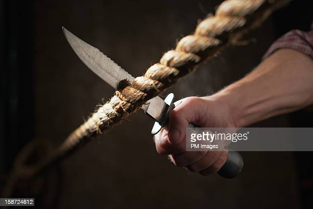 Man cuts rope with big knife