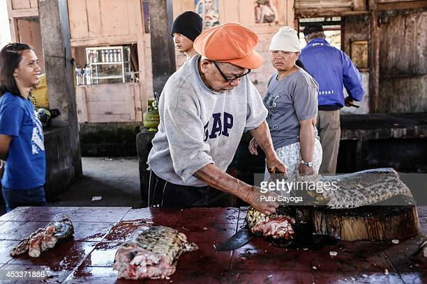 A man cuts snake at Langowan traditional market on August 9 2014 in Langowan North Sulawesi The Langowan traditional market is famous for selling a...