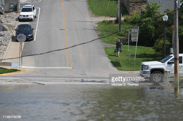 A man cuts the grass as flooding from the Mississippi River inundates a neighborhood on June 7 2019 in Grafton Illinois Residents along Mississippi...