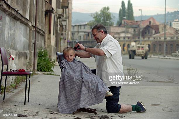A man cuts the hair of a young boy during a lull in shooting in Sniper Alley During the 47 months between the spring of 1992 and February 1996 the...