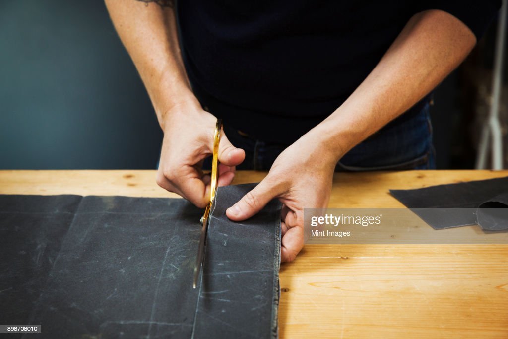 A man cutting a piece of grey fabric with shears. : Stock Photo