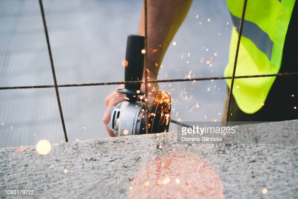 Man cutting a wire with an electric cutter