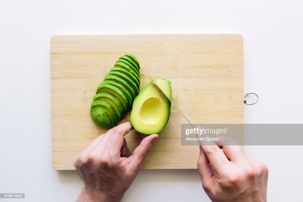 Man cutting avocado on a wooden cutting board, personal perspective directly above view : Stock Photo