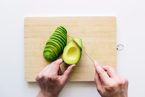 Man cutting avocado on a wooden cutting board, personal perspective directly above view - gettyimageskorea