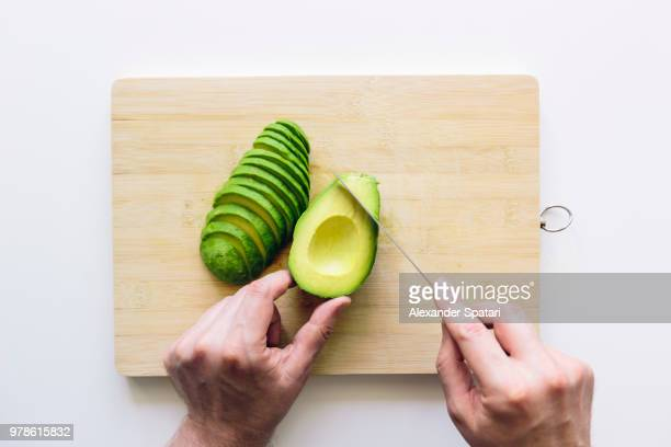 man cutting avocado on a wooden cutting board, personal perspective directly above view - chop stock pictures, royalty-free photos & images