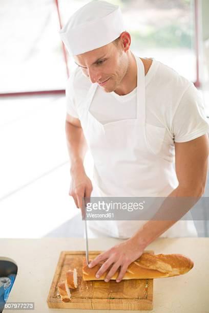 Man cutting baguette