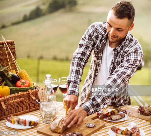 hombre cortando pan en la fiesta de barbacoa