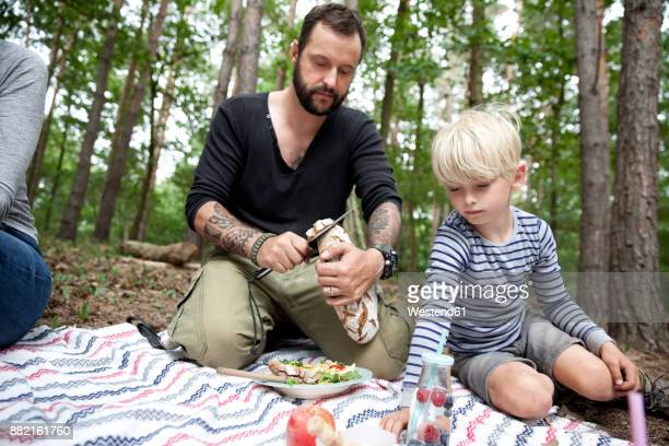 Man cutting bread during a picnic in forest