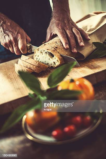 Man cutting bread in rustic kitchen