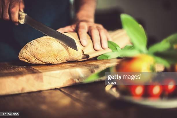 Man cutting bread in rustic kitchen