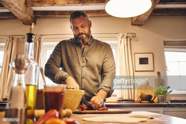 man cutting fresh vegetables in kitchen - dean foods stock photos and pictures