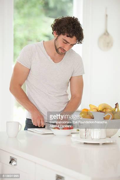 Man cutting fruit in kitchen