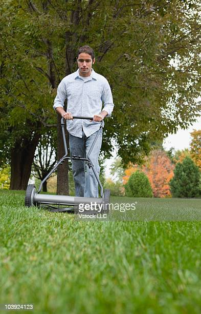 Man cutting grass with push mower