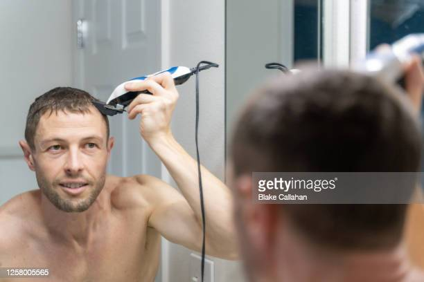 man cutting his own hair - shaved stock pictures, royalty-free photos & images