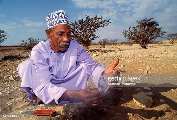 Man cutting incense tree bark, Wadi Adonob, Salalah, Oman
