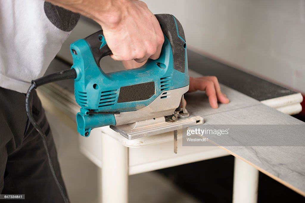 Man cutting laminate floor pieces with a jigsaw : Stock Photo