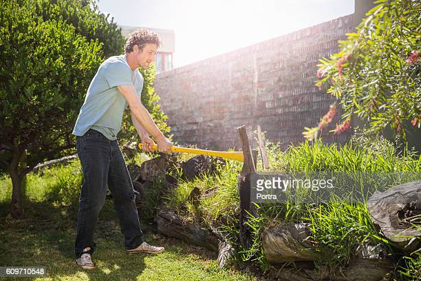 Man cutting logs with axe in yard on sunny day