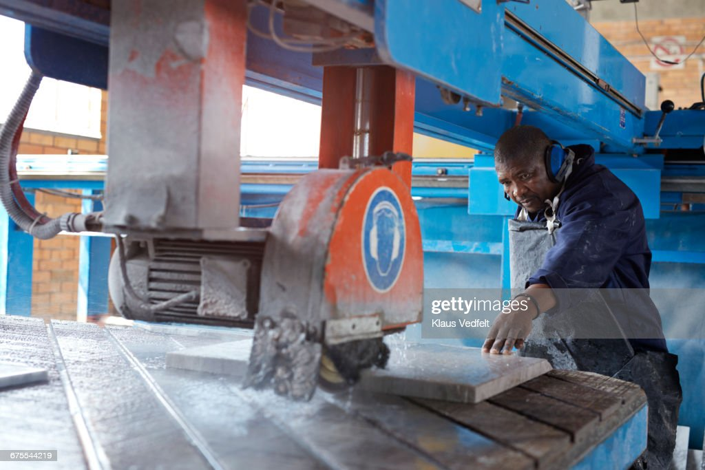 Man cutting marble slab at factory : Stock Photo
