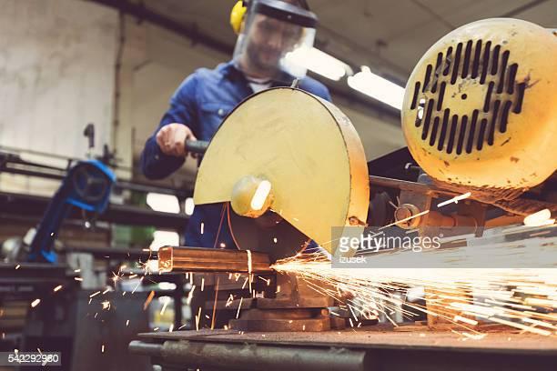 Man cutting metal bar in a workshop, using grinder