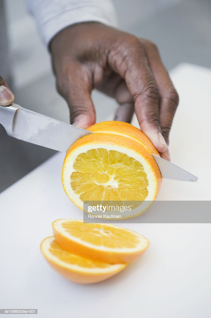 Man cutting orange on chopping board, close-up : Foto stock
