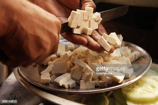 Man Cutting Paneer Into Pieces