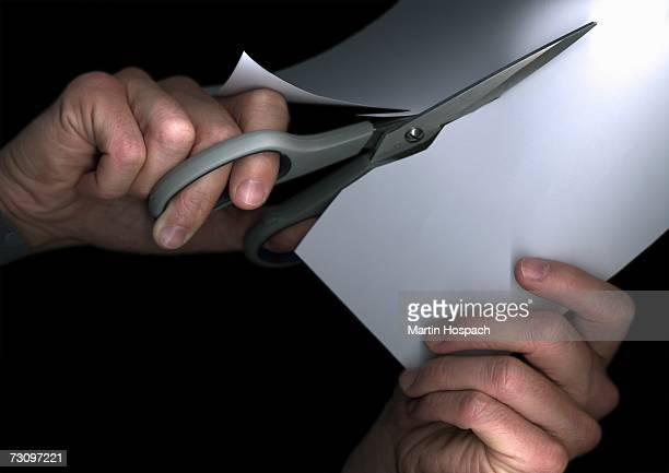 Man cutting paper with scissors