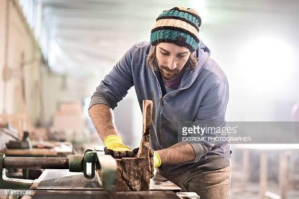 man cutting piece of wood - rolled up sleeves stock pictures, royalty-free photos & images