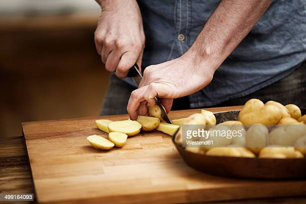 man cutting potatoes in kitchen - raw potato stock pictures, royalty-free photos & images