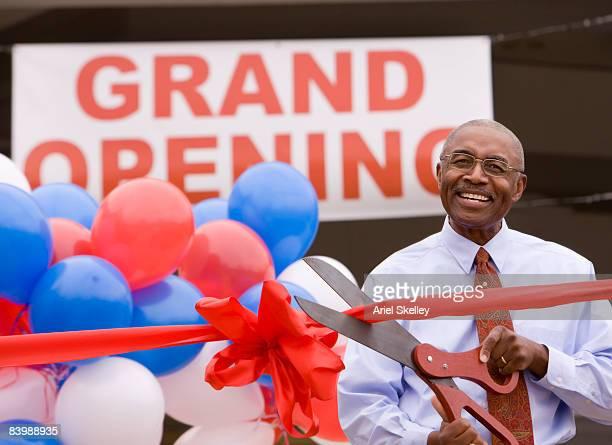 Man Cutting Ribbon at Grand Opening Celebration