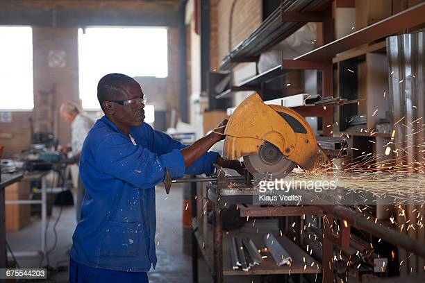 Man cutting steel pipe at factory