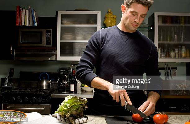 Man cutting tomatoes in domestic kitchen