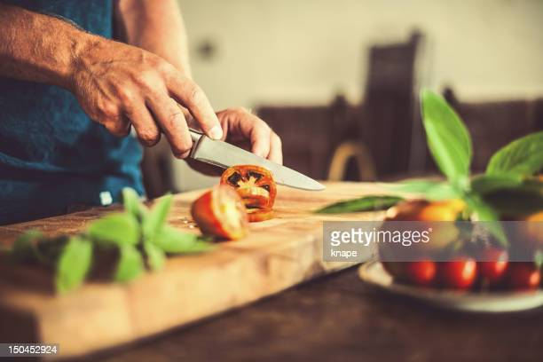 Homme coupe tomates dans cuisine rustique