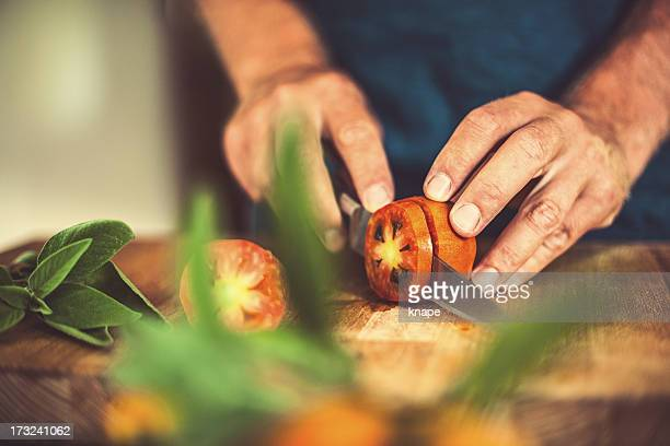 man cutting tomatoes in rustic kitchen - chop stock pictures, royalty-free photos & images