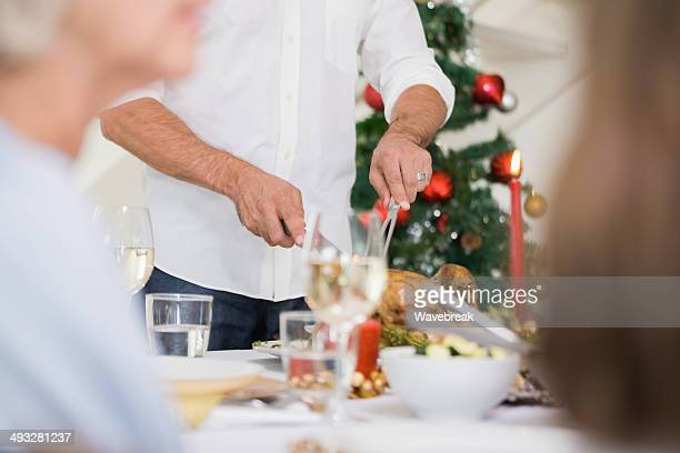 Man cutting turkey roast at dining table for christmas dinner