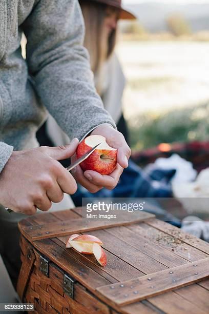 A man cutting up an apple with a sharp knife.