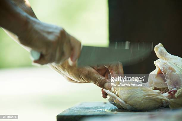 'Man cutting up chicken, blurred motion, close-up'