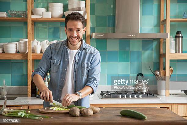 Man cutting up ingredients in kitchen, portrait