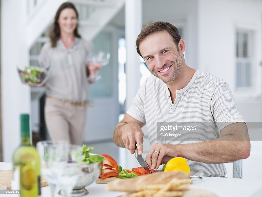 Man cutting vegetable with woman in the background : Stock Photo