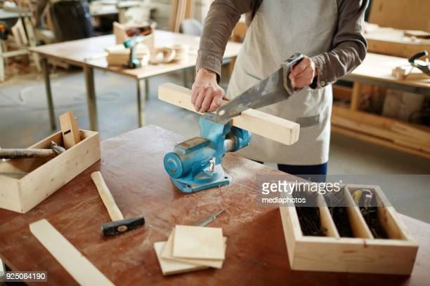Man cutting wooden plank with saw