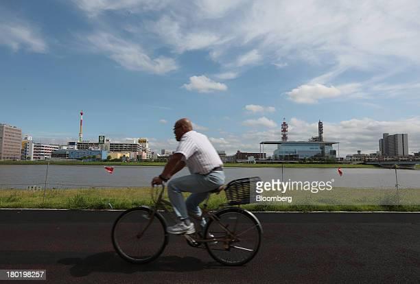 A man cycles along the bank of the Shinano river in Niigata City Niigata Prefecture Japan on Friday Sept 6 2013 Niigata Governor Hirohiko Izumidas...
