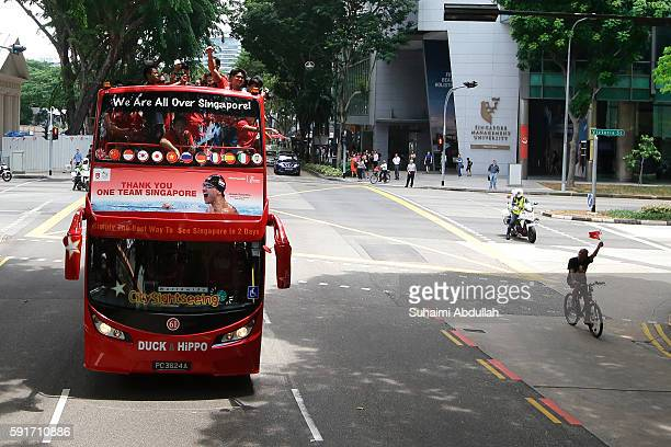 A man cycles and waves alongside Singaporean Swimmer Joseph Schooling onboard the open top bus during his victory parade on August 18 2016 in...