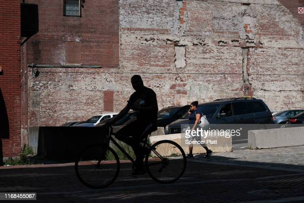 A man cycles down a street in Lawrence on August 16 2019 in Lawrence Massachusetts Lawrence once one of America's great manufacturing cities with...