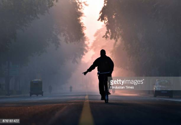 A man cycles early morning after late night drizzling helped to lower the smog and pollution level at Crescent road on November 18 2017 in New Delhi...