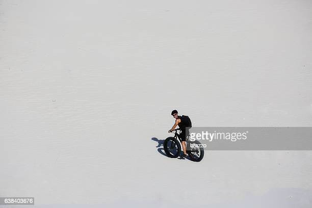 Man cycles in the sand on a fatbike