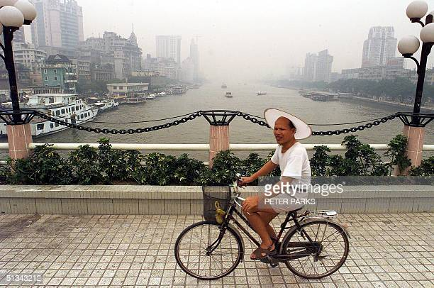 A man cycles on a bridge over the Pearl River in Guangzhou 06 July 2000 Guangzhou the capital of Guangdong province is one of China's most prosperous...