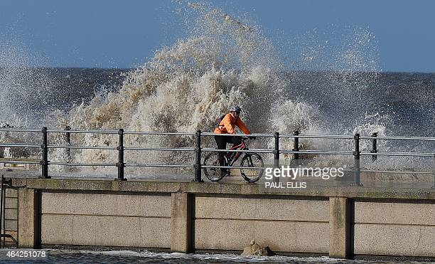 A man cycles on the path between the marine lake and the coastal wall at New Brighton north west England on February 23 2015 as waves from the Irish...