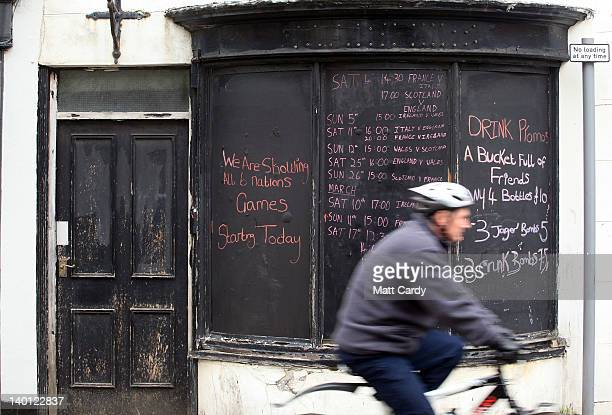 A man cycles pass a pub advertising drink promotions close to one of the main shopping streets in Weymouth town centre on February 28 2012 in...