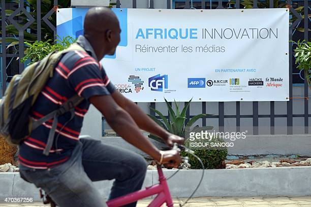 A man cycles past a banner for 'Afrique Innovation' during a 48hour 'hackathon' event in which seven teams compete to develop innovative applications...